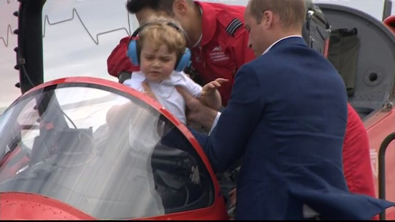 The Duke of Cambridge lifts his son Prince George into the cockpit of a Red Arrows jet for his first taste of sitting at the controls.