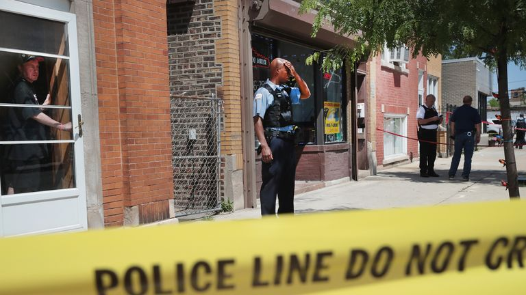 Police investigate a crime scene after two people were shot in the Westside area of Chicago in June