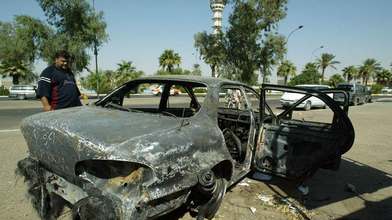 An Iraqi looks 24 September 2007, at a burnt car on the site where Blackwater guards who were escorting US embassy officials opened fire in the western Baghdad neighbourhood of Yarmukh