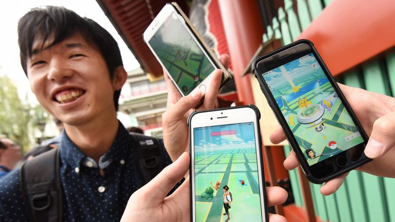 Japanese students display their phones as they play Nintendo's Pokemon Go game on their mobiles in Tokyo as the game was finally launched in its native market