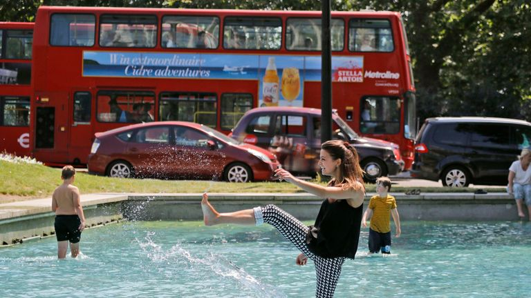 A woman cools herself in the fountain at Marble Arch in central London