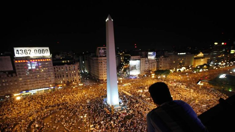 A man watches as protesters demonstrate during a march against Argentina's President Cristina Fernandez