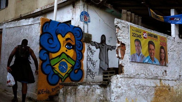 A man walks past graffiti and a political banner at the Cerro Cora slum in Rio de Janeiro