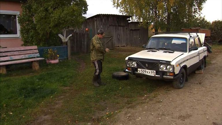Men work on a car in a rural Russian town