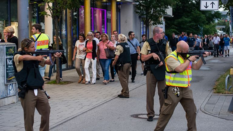 Officers guard with guns as other officers escort people from inside the shopping centre