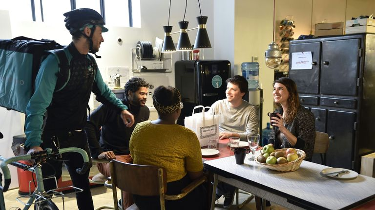 A Deliveroo biker delivers meals to people taking a lunch break in Paris.