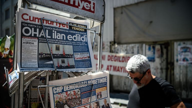 A man reads the newspaper front pages after the failed coup