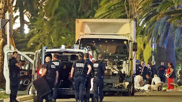 Police stand by as medics treat a victim of the truck attack in Nice