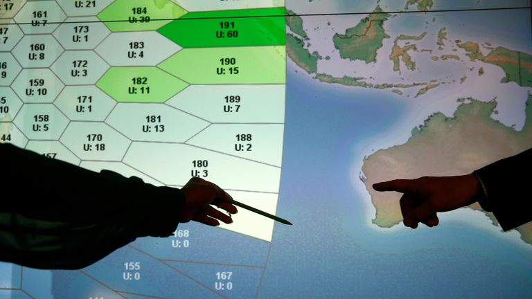 A person involved in the search points to a section of the screen showing a part of the southern Indian Ocean