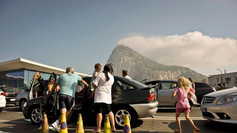People get out of their cars to cool down as they wait in traffic queues on the Gibraltar side of the Spanish border