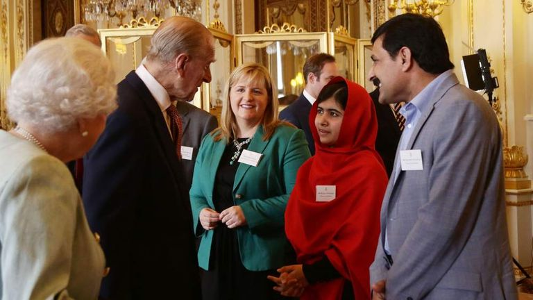 Malala meets the Duke of Edinburgh as the Queen and her father look on