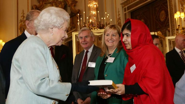 Malala hands a book to the Queen