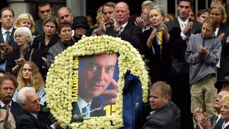 Relatives and friends of Pim Fortuyn hold up a crown of roses with a picture of him after the funeral mass