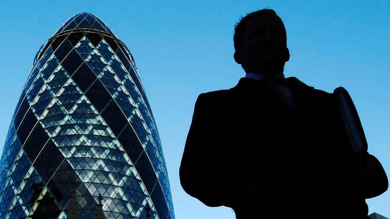 A City worker walks near the Swiss Re building known as the Gherkin
