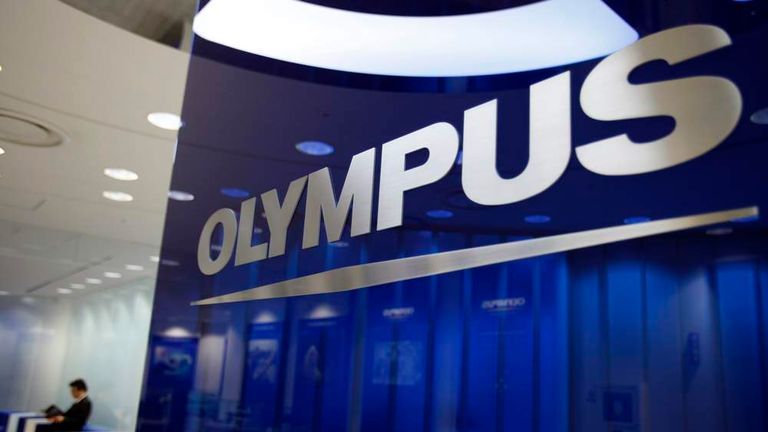 A man sits near a logo of Japan's Olympus at the company headquarters in Tokyo