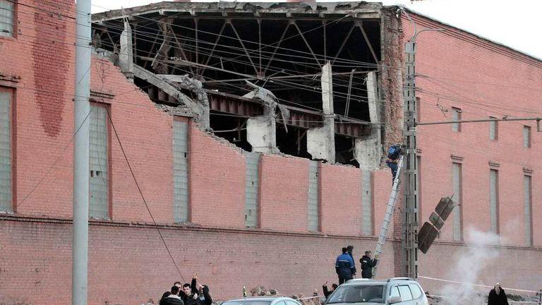 Workers examine damage on buildings in Chelyabinsk