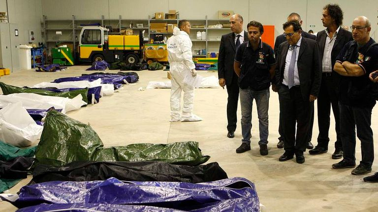 President of Sicily region Rosario Crocetta stands in front of body bags containing African migrants, who drowned trying to reach Italian shores, lying in a hangar of the Lampedusa airport