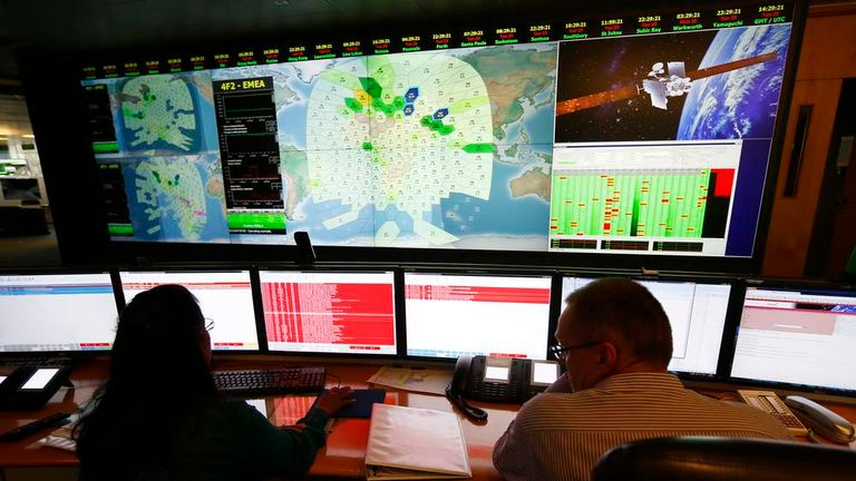 Staff at satellite communications company Inmarsat work in front of a screen showing subscribers using their service throughout the world, at their headquarters in London