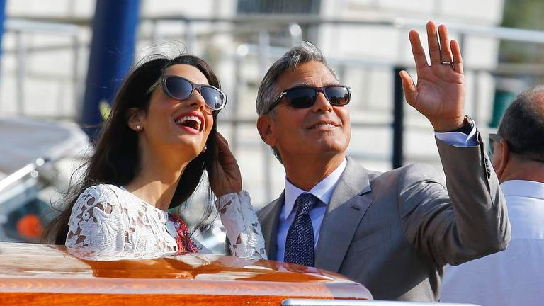 U.S. actor George Clooney and his wife Amal Alamuddin stand on a water taxi as they leave the seven-star hotel Aman Canal Grande Venice in Venice
