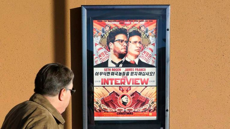 """A man walks by poster for film """"The Interview"""" outside Alamo Drafthouse theater in Littleton"""