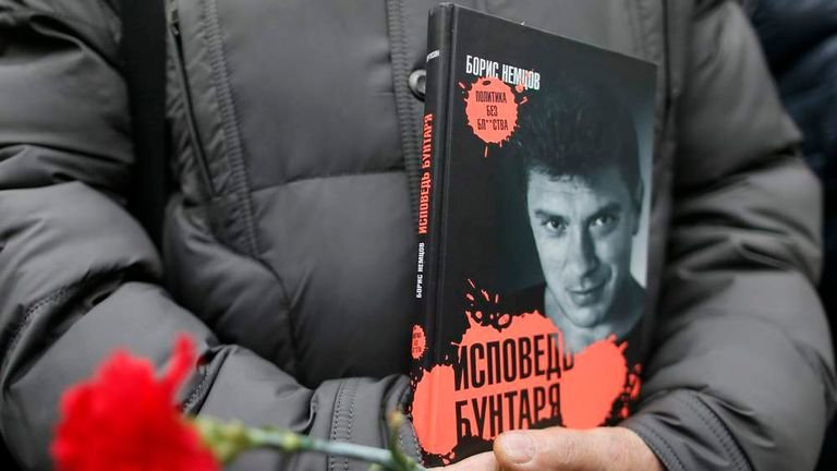 Visitor holds flowers and a book by Russian leading opposition figure Nemtsov before funeral in Moscow