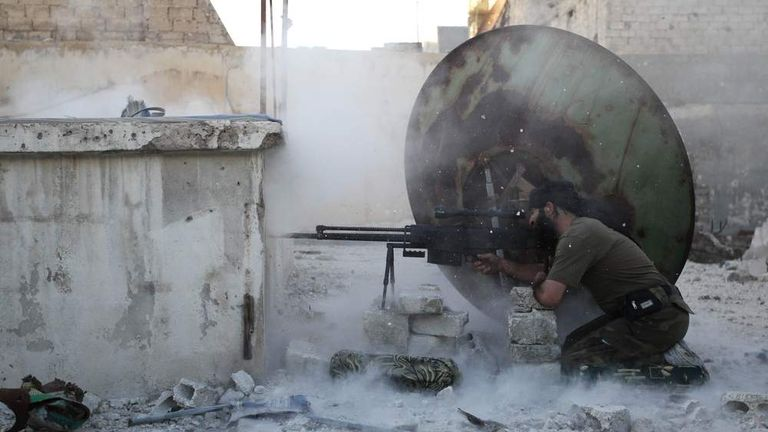 A member of the Free Syrian Army shoots back at a sniper during what activists said were clashes with pro-government forces in Aleppo's Karm al-Jabal district.