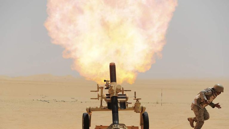 A Saudi soldier fires a mortar towards Houthi movement position, at the Saudi border with Yemen