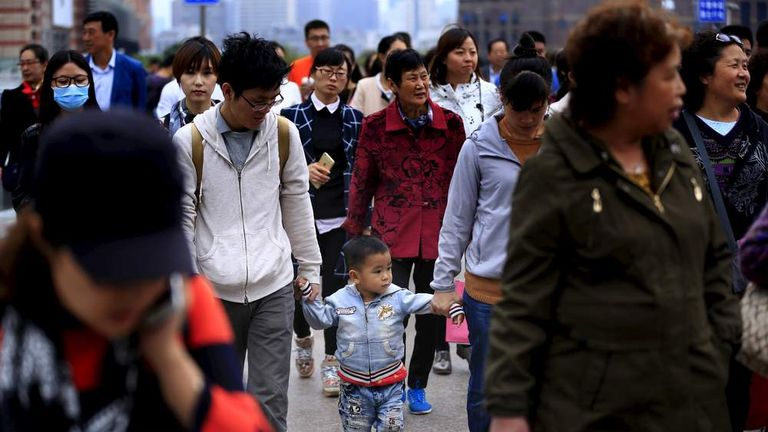 A little boy walks with his parents on a bridge in Shanghai.