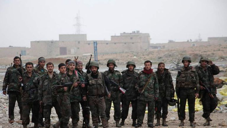 Syrian army soldiers loyal to President al-Assad pose for photograph with weapons in Aleppo town of Naqaren
