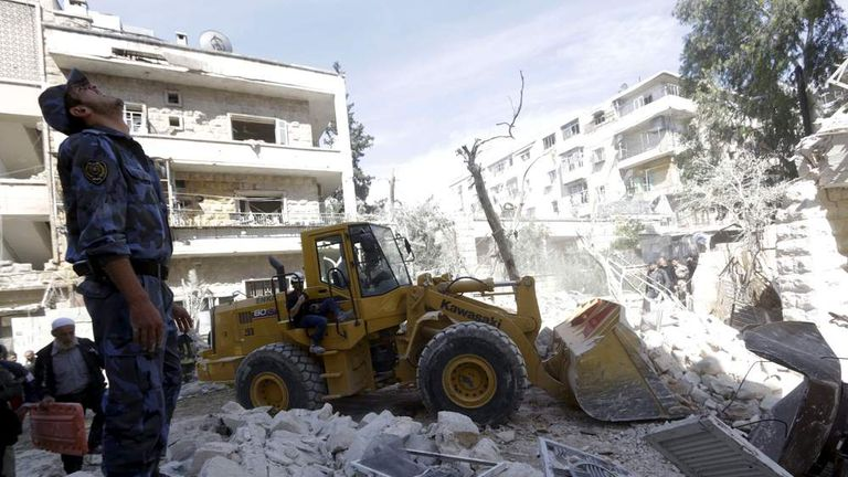 A Civil Defence member looks at the sky fearing another airstrike as he searches for survivors at a damaged site after what activists said was a barrel bomb dropped by forces loyal to Syria's President Bashar al-Assad