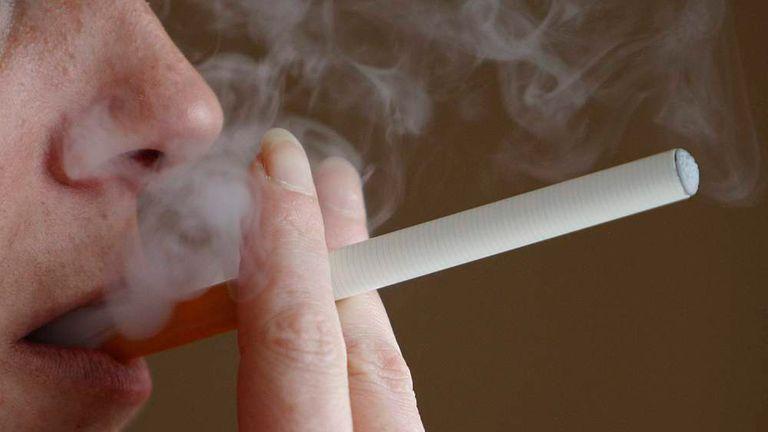 A woman smokes an E-cigarette, an electronic substitute