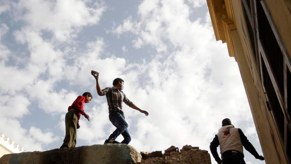 Egyptian demonstrators stand on a wall erected by security and hurl rocks at riot police in Tahrir Square