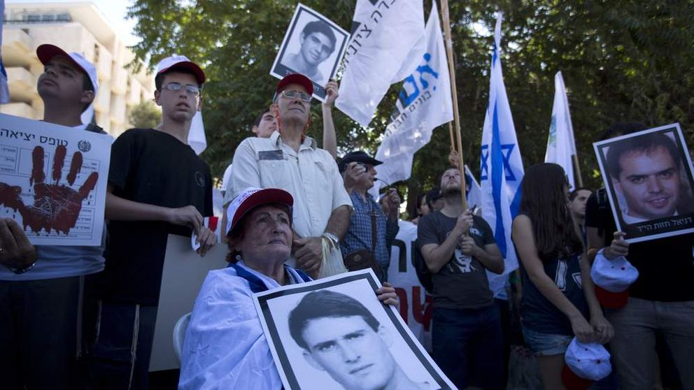 Israelis holding pictures of their loved ones