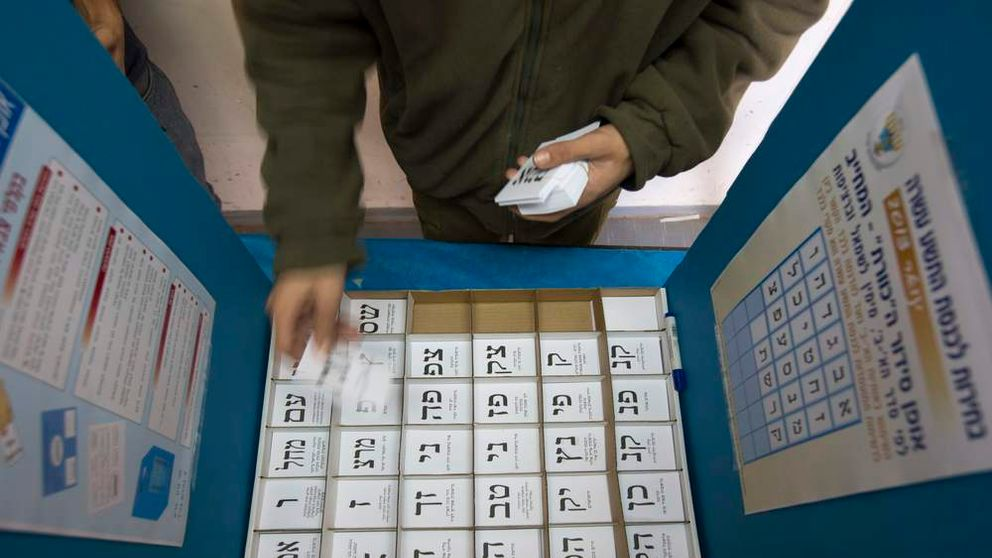 An Israeli soldier arranges ballots in a voting booth in a military base in southern Israel
