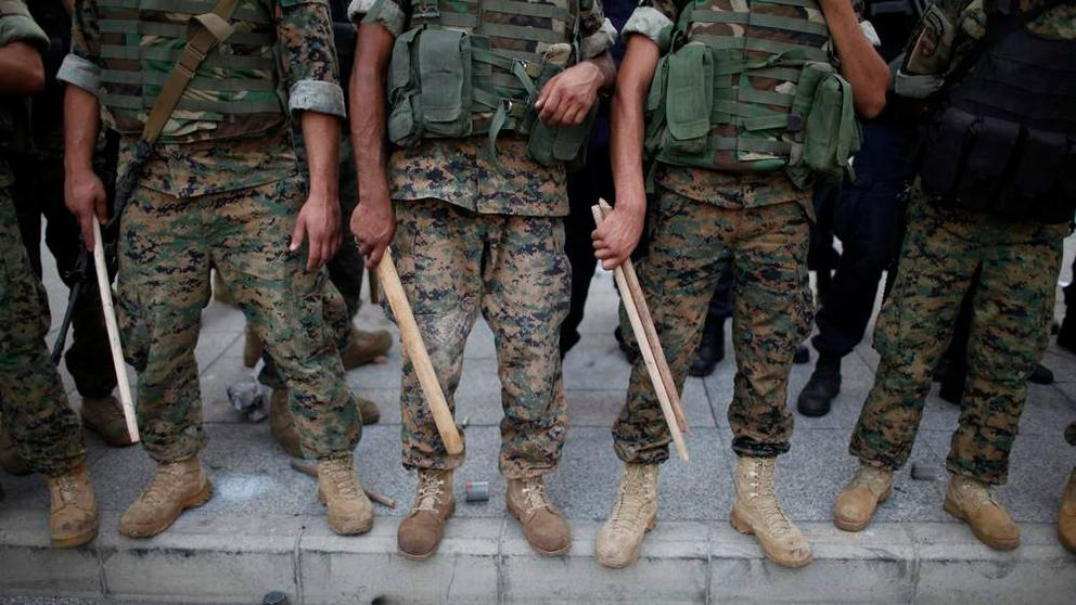 Lebanese army soldiers hold sticks as they secure the area around the government palace in Beirut
