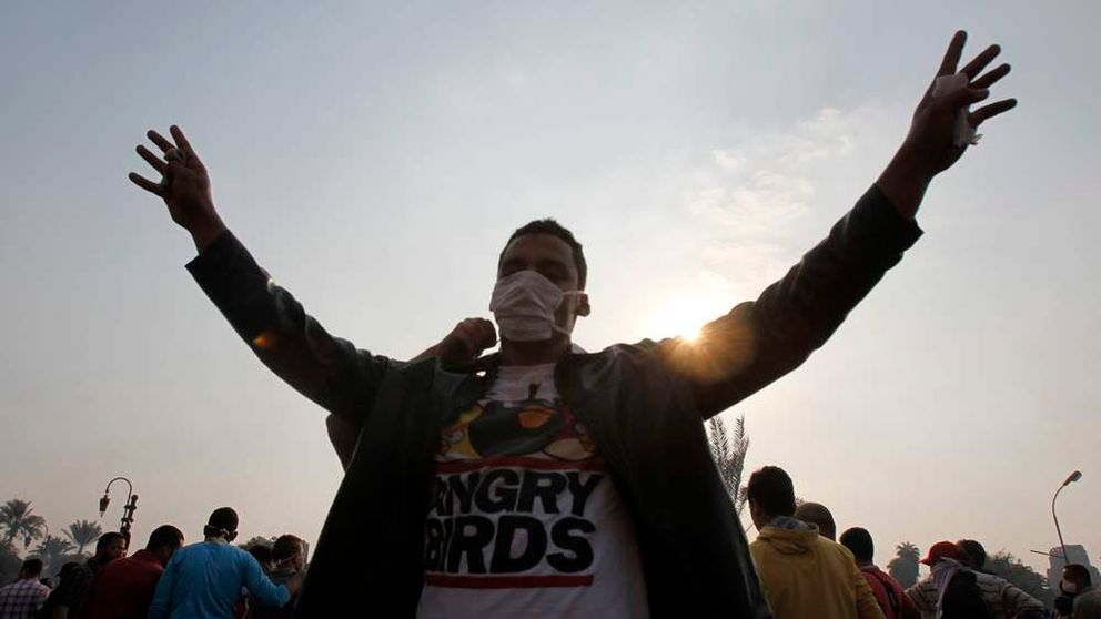A member of the Muslim Brotherhood and supporter of Mursi gestures the number four, in front of riot police in Cairo