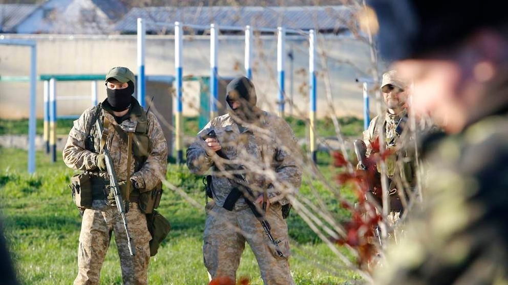 Armed men, believed to be Russian servicemen, stand guard at a military airbase in the Crimean town of Belbek near Sevastopol