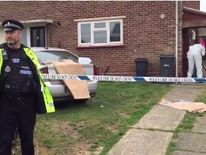 A police officer outside the home in Halstead, with forensic officers in a garage