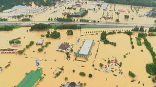 Three people have died and thousands rescued in the 'historic' floods