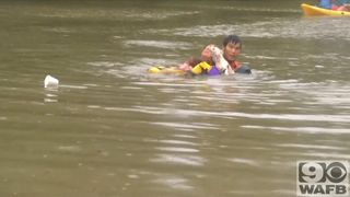A drowning woman and her dog are pulled from a submerged car in the nick of time