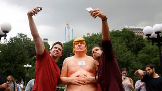 People pose for selfies with a naked statue of U.S. Republican presidential nominee Donald Trump that was left in Union Square Park, New York City