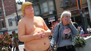 A passerby has a picture taken with a statue depicting republican presidential nominee Donald Trump in San Francisco
