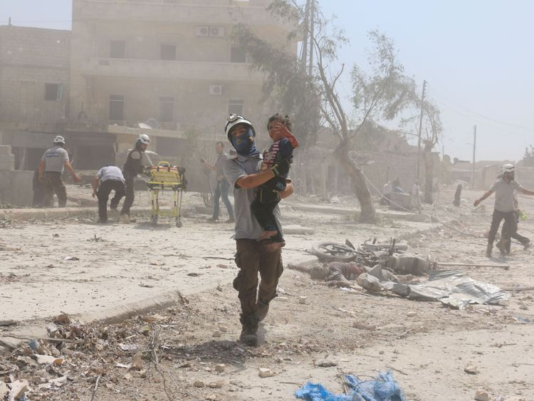 A Syrian rescuer carries a child in the Maadi district of eastern Aleppo after a barrel bomb attack