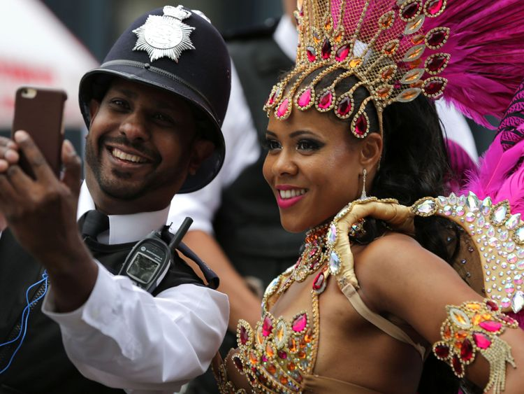 A performer poses for a selfie with a police officer on the second day of the Notting Hill Carnival in west London