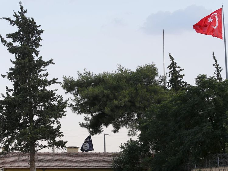 An IS flag and a Turkish flag at Karkamis, just over the border from Jarabulus