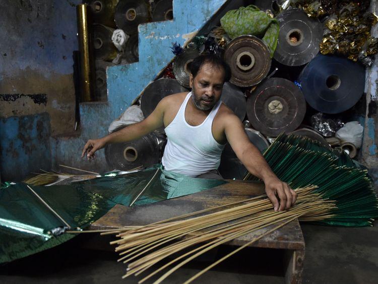 A kite maker works in his workshop in New Delhi