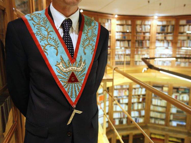 A worshipful master poses in his masonic regalia at a grand lodge