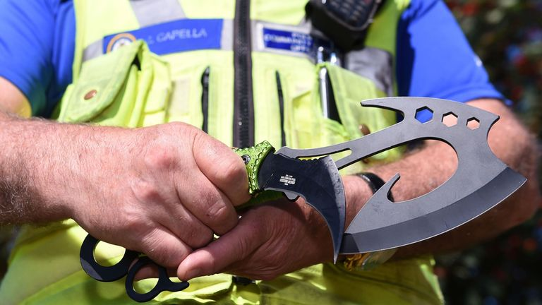 A police officer holds two examples of 'zombie knives'