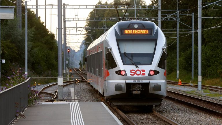 A train displays a sign saying 'do not enter' as investigators examine the scene