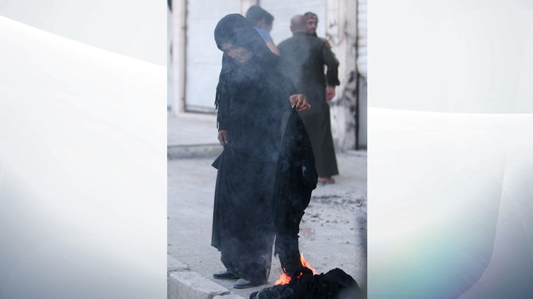 A woman sets fire to a niqab after she was evacuated with others by the Syria Democratic Forces (SDF) fighters from an Islamic State-controlled neighbourhood of Manbij, in Aleppo Governorate, Syria